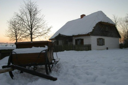 Sanie na tle chaty z Muzeum Wsi Mazowieckiej w Sierpcu